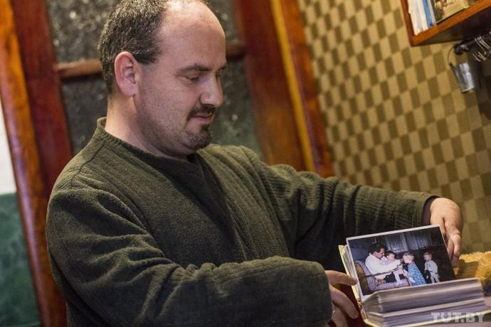 Борис показывает фотографии маленькой Анны во время посещения дома-интерната