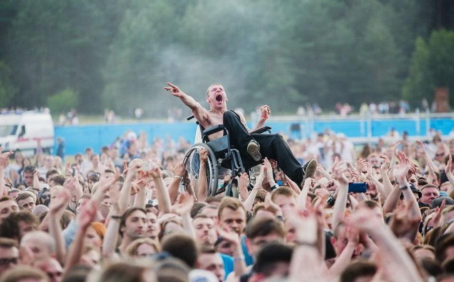 Парень на коляске, которого подняли над толпой на