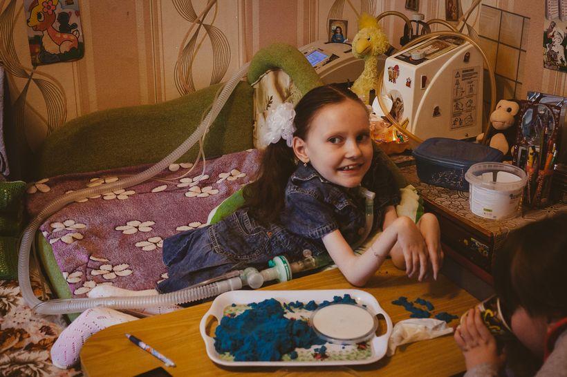 Ангелина (9 лет, СМА II типа). Семья Ангелины переехала в Минск недавно. Потому что за пределами Минска специалистов и необходимого «эквипмента» нет. В городе, где раньше жила девочка, вызвали врача подключить ее к аппарату ИВЛ. Врач увидела девочку, ее тоненькие ручки, странную фигурку и личико, уточнила диагноза и отказалась производить манипуляции, потому что не знает, что с этим всем делать. Из хорошего, обжитого дома семья переехала в самую дешевую съемную квартиру в Минске, где при подъезде даже пандуса нет. Фото: Александр Васюкович, Имена