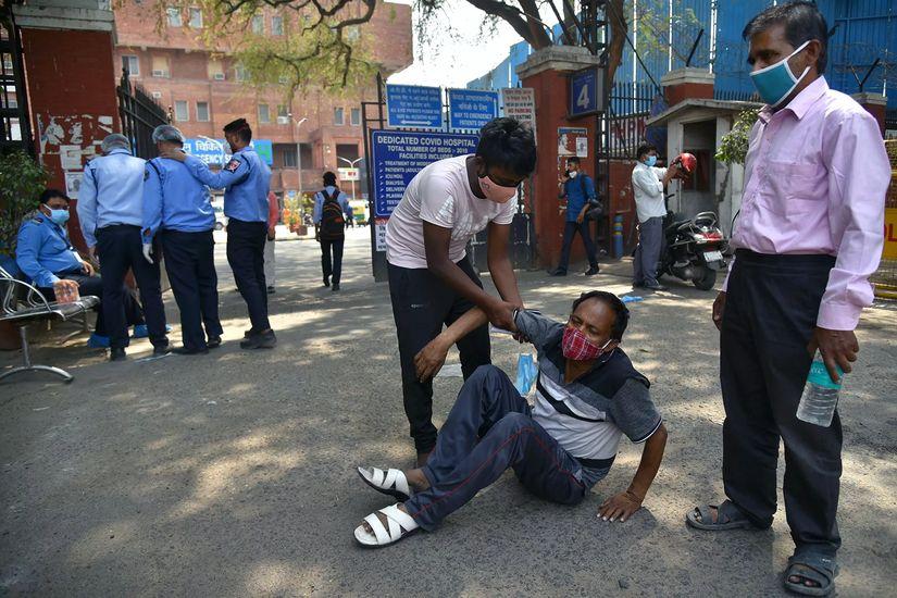 Мужчина помогает подняться упавшему у входа на территорию госпиталя в Дели